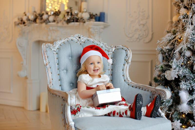 Małej dziewczynki powabna blondynka w czerwonym Santa kapeluszu, ono uśmiecha się i zdjęcie stock