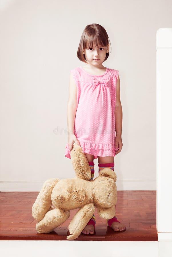 Małej dziewczynki pozycja i mienie miś fotografia stock