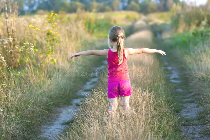 Małej dziewczynki pozycja na śródpolnej drodze na lato zmierzchu wieczór zdjęcie stock