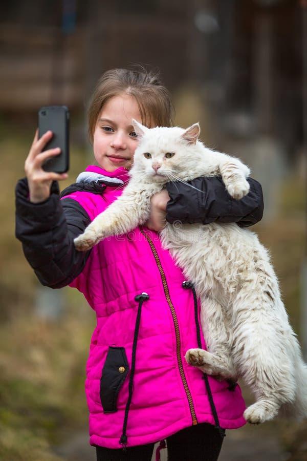 Małej dziewczynki pozycja na ulicie bierze selfie z przybłąkanym kotem Miłość obraz stock