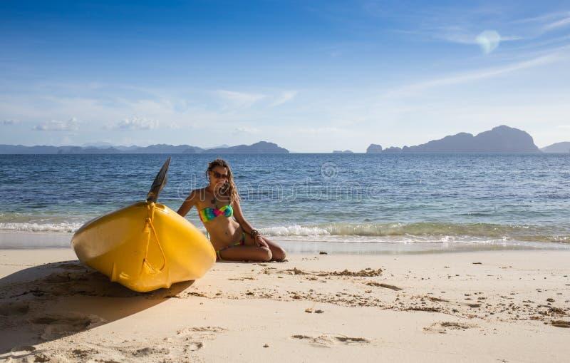 Małej dziewczynki pozycja obok kolorowego żółtego kajaka obrazy stock