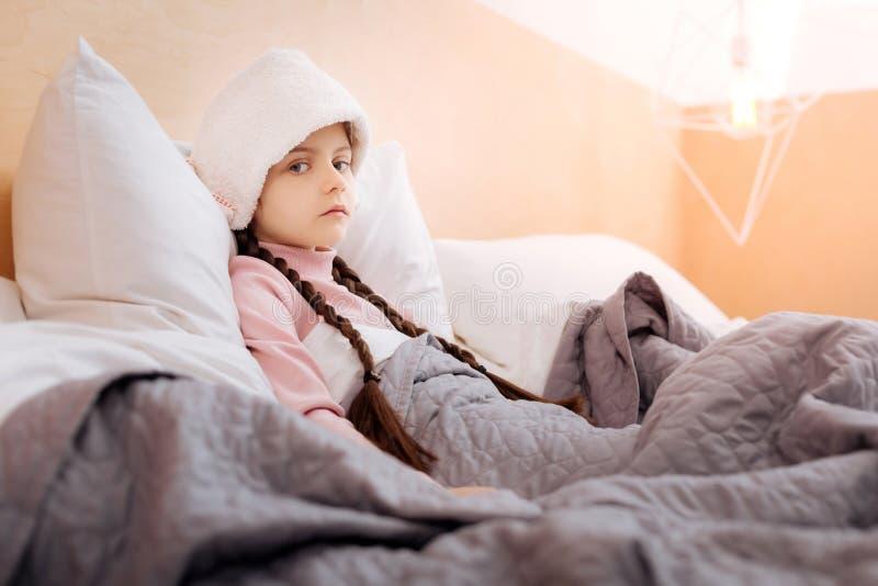 Małej dziewczynki przyglądający zmęczony podczas gdy zakrywający z miękką koc obrazy royalty free