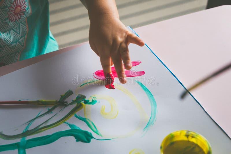 Małej dziewczynki ręka która maluje z jej palcem, obrazy stock