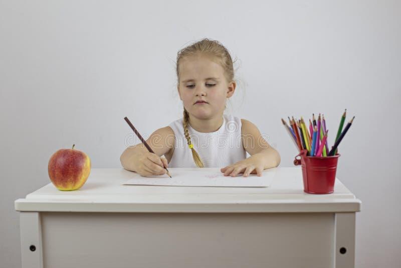 Małej dziewczynki uczennica pisze w ołówku na prześcieradle papier zdjęcia stock