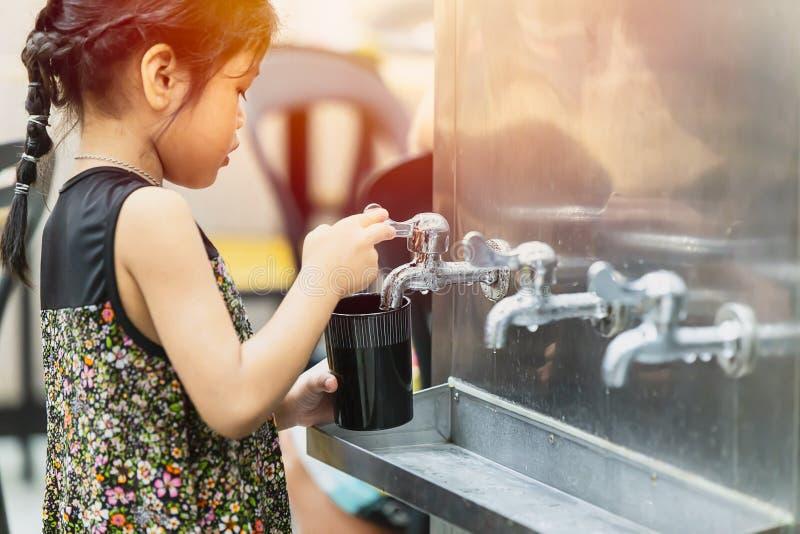Małej dziewczynki woda pitna od jawnego chłodniczego zbiornika obraz royalty free
