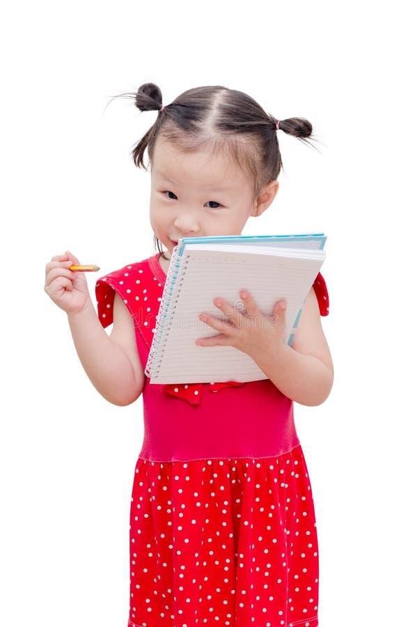 Małej dziewczynki writing na notatniku nad bielem zdjęcia royalty free
