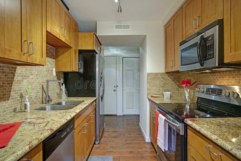 Małej galery kuchenny projekt z czarnymi kuchennymi urządzeniami zdjęcie royalty free