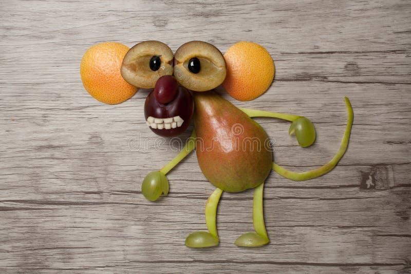 Małpa robić z owoc na drewnianym tle obraz stock