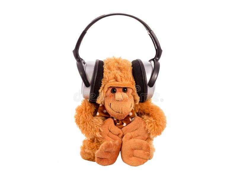Małpuje miękką zabawkę w słuchawkach zdjęcie royalty free