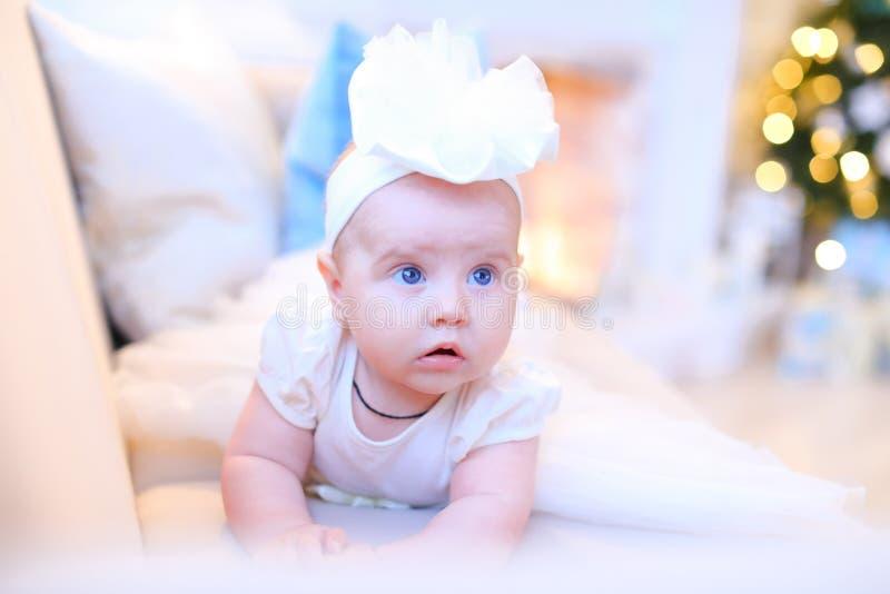 Mały ładny żeński dziecko kłama na kanapie i jest ubranym biel ubrania z niebieskimi oczami obraz royalty free