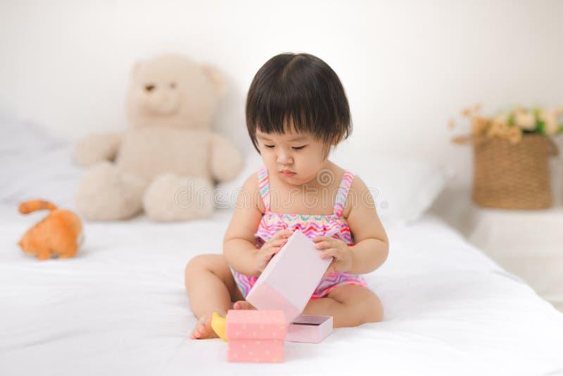 Mały śliczny azjatykci dziewczynki obsiadanie na łóżkowy bawić się obraz royalty free