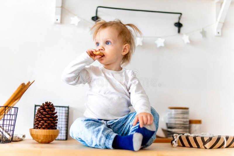 Mały śliczny berbeć dziewczyny łasowania owsa ciastko i obsiadanie na kuchennym stole obrazy royalty free