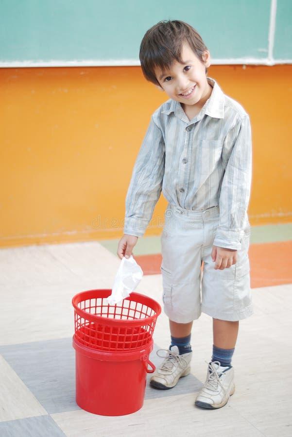 Mały śliczny chłopiec miotania papier wewnątrz przetwarza kosz obraz stock
