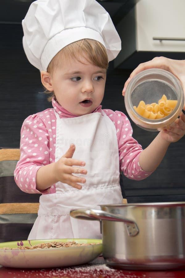 Mały śliczny dziecko nalewa makaron w niecce w kuchni fotografia stock