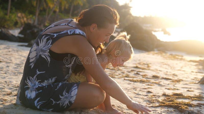 Mały śliczny dziewczyny dziecko, potomstwa i matkujemy obsiadanie przy tropikalną plażą podczas pięknego zmierzchu obraz stock