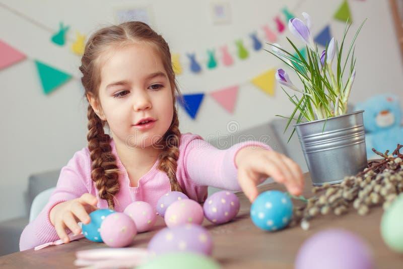 Mały śliczny dziewczyny Easter świętowania pojęcia obsiadanie bawić się z jajka zakończeniem w domu zdjęcia stock