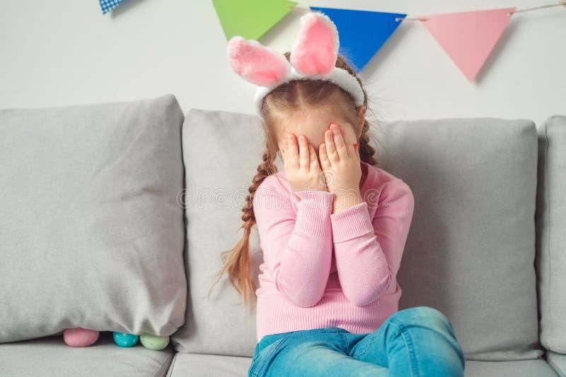 Mały śliczny dziewczyny Easter świętowania pojęcie w królików ucho płacze spęczenie w domu obrazy stock