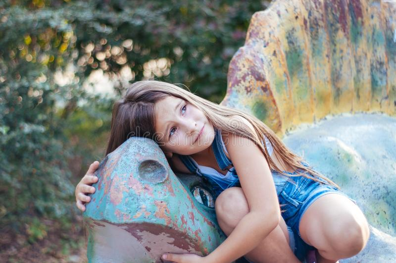 Mały śliczny dziewczyny obsiadanie na dinosaur statui w parkowym lecie obrazy stock