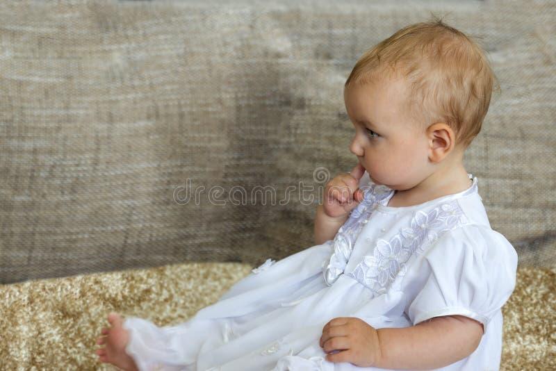 Mały śliczny dziewczyny obsiadanie na dywanowym mieniu jej palec w jej usta obrazy stock