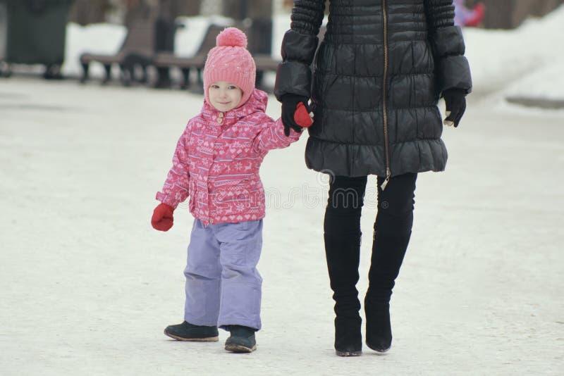 Mały śliczny dziewczyny odprowadzenie w śniegu i spadać w snowbank dla spaceru z jej mamą fotografia royalty free
