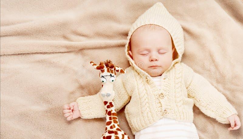 Mały śliczny nowonarodzony chłopiec dosypianie z żyrafą fotografia stock