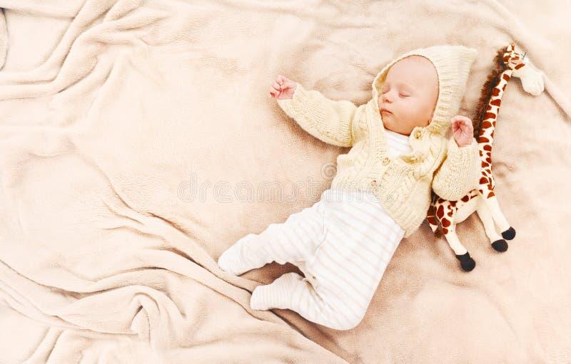 Mały śliczny nowonarodzony chłopiec dosypianie z żyrafy zabawką zdjęcia royalty free