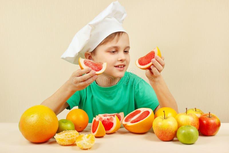 Mały śmieszny szef kuchni z dwa plasterkami grapefruitowy przy stołem z owoc zdjęcia stock
