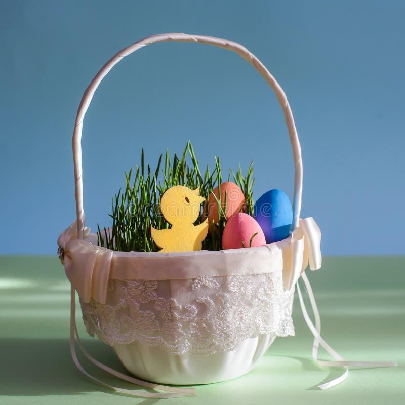 Mały żółty kurczak w koszu z Wielkanocnymi jajkami obraz royalty free