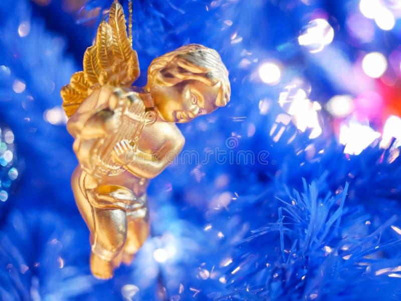 mały anioł Bożego Narodzenia wiszący dekoracje na niebieskim tle obraz stock