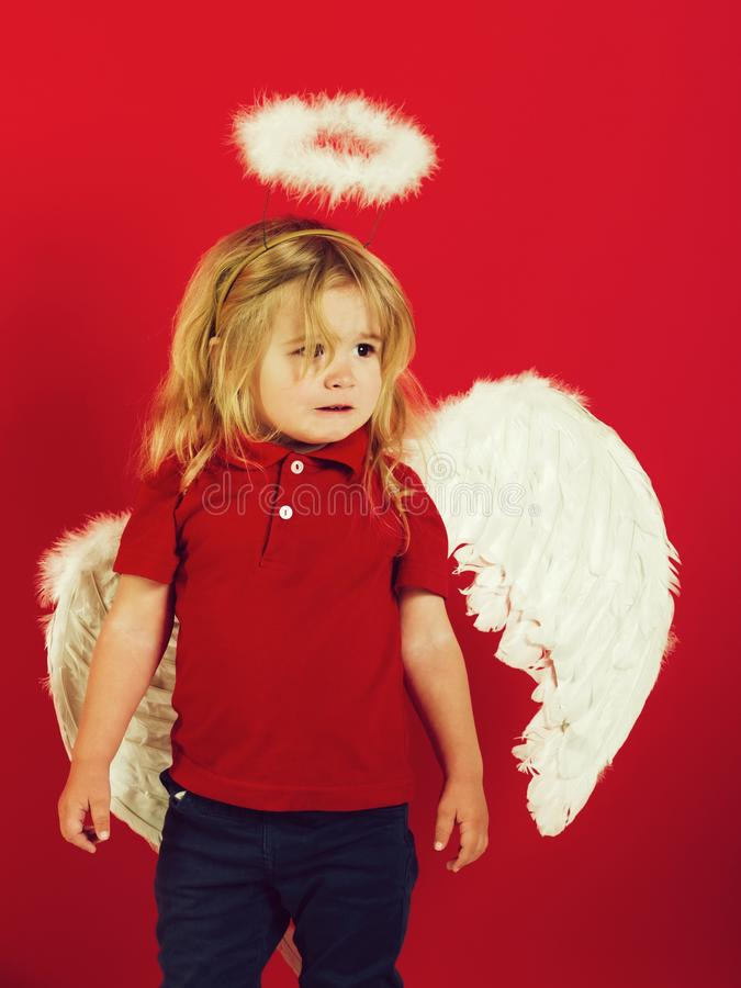 mały anioł chłopiec płacz z białego piórka halo i skrzydłami obraz royalty free