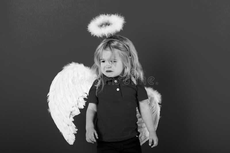 mały anioł chłopiec płacz z białego piórka halo i skrzydłami zdjęcia royalty free