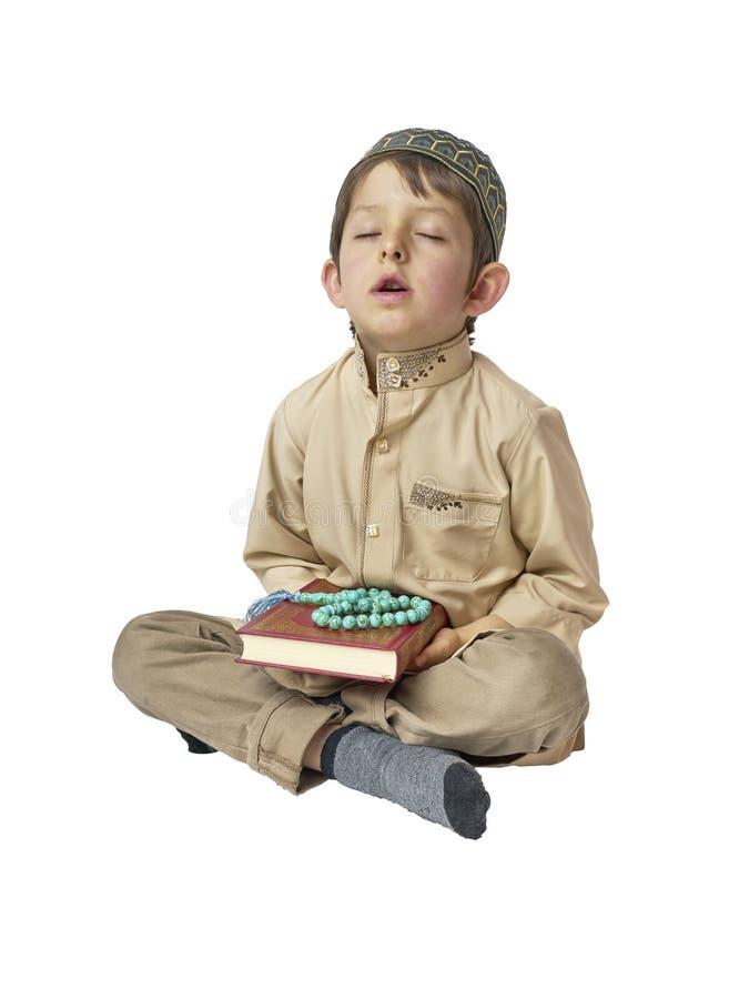 Mały arabski chłopiec modlenie święty Koran z modlitewnymi koralikami na białym tle i mienie zdjęcia stock