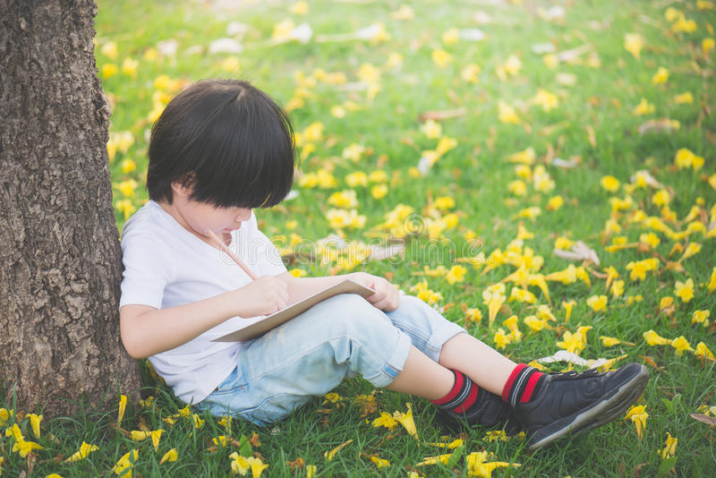 Mały Azjatycki chłopiec obsiadanie pod drzewem i rysunek w notatniku obrazy stock