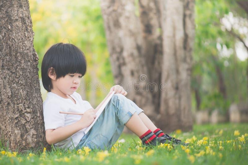 Mały Azjatycki chłopiec obsiadanie pod drzewem i rysunek w notatniku zdjęcie stock