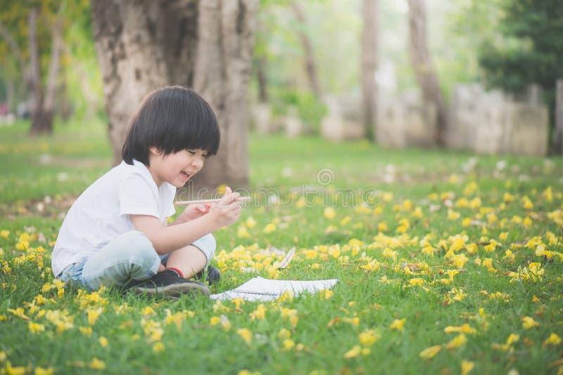 Mały Azjatycki chłopiec obsiadanie pod drzewem i rysunek w notatniku fotografia stock