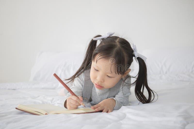 Mały Azjatycki dziewczyny lying on the beach na łóżka i writing abecadle na notatniku obrazy stock