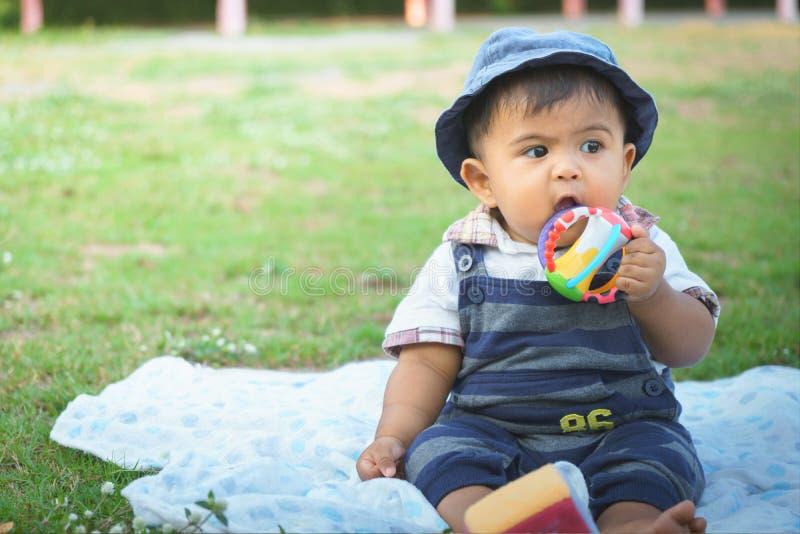 Mały azjatykci dziecka obsiadanie w ogródzie, rocznika brzmienie obraz stock