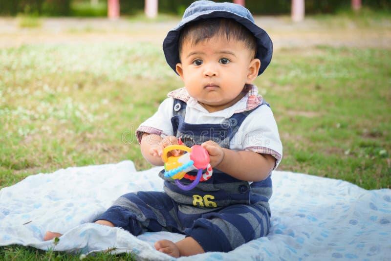 Mały azjatykci dziecka obsiadanie w ogródzie, rocznika brzmienie obrazy royalty free
