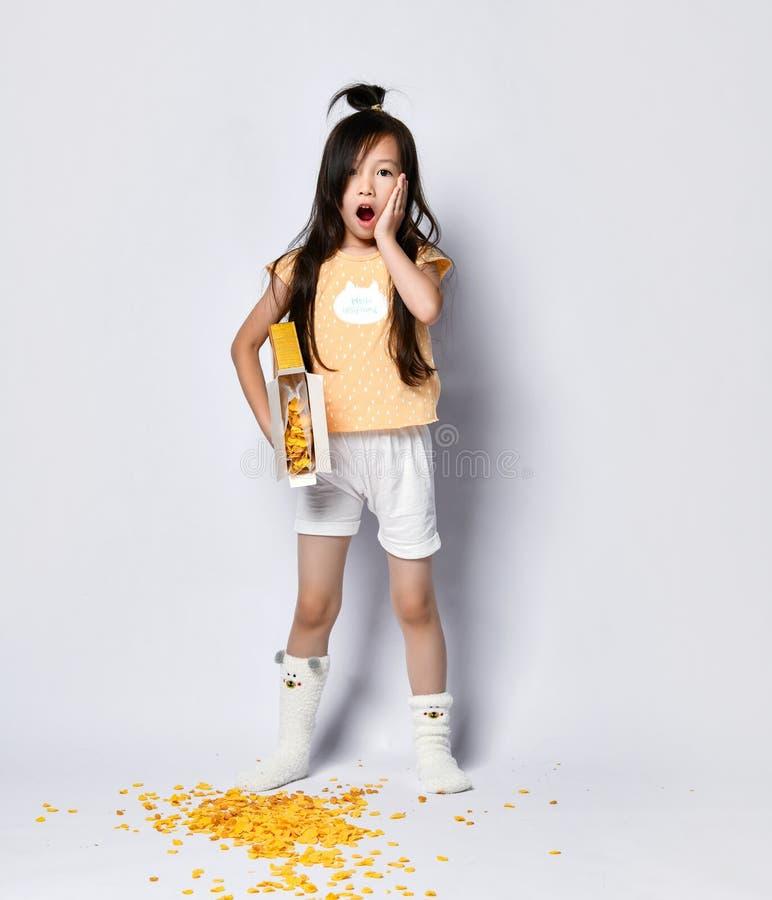 Mały azjatykci dziewczyna dzieciak w domów ubraniach martwi się o jej niepowodzeniu z kukurydzanymi płatkami podczas śniadaniowyc obrazy stock