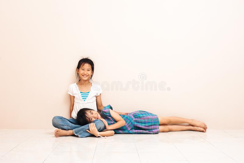 Mały azjatykci dziewczyny obsiadanie z jej starą siostrą na podłodze w domu uroczy powiązanie fotografia royalty free