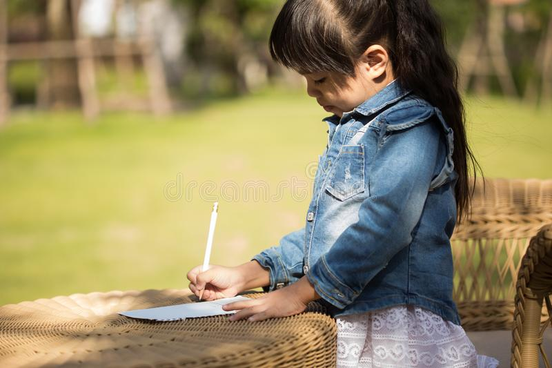 Mały azjatykci dziewczyny writing na notatniku w parku zdjęcia stock