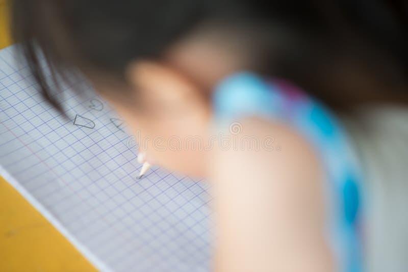 Mały azjatykci dziewczyny writing w notatnik szkole fotografia royalty free