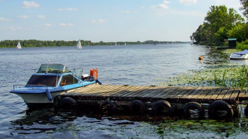 Mały, błękitny motorboat cumujący drewniana gang deska, fotografia royalty free