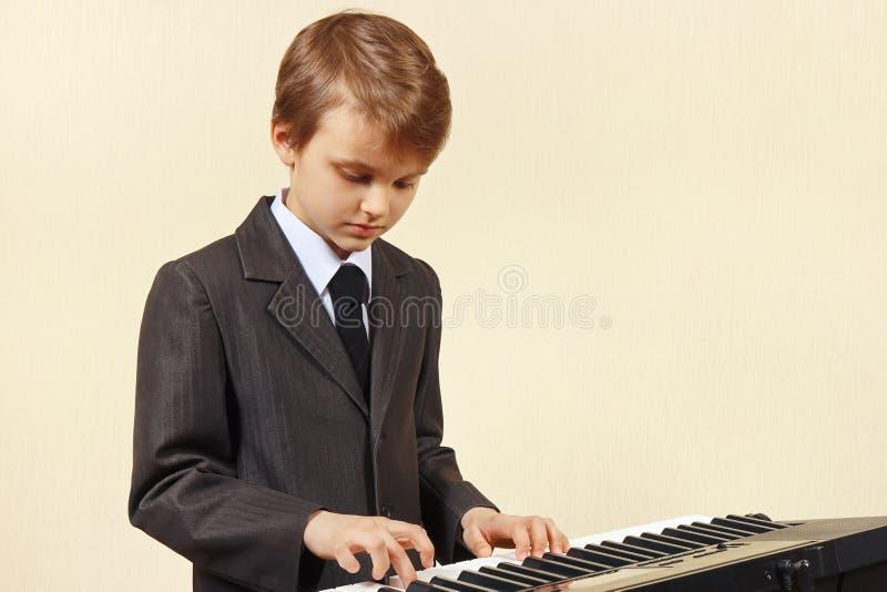 Mały beginner muzyk w kostiumu bawić się syntetyka obraz stock
