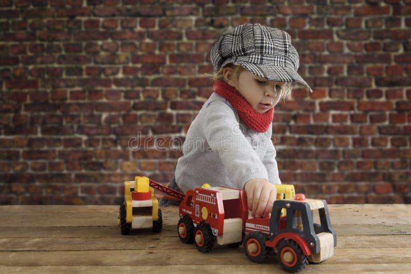 Mały berbeć bawić się z drewnianymi samochodami zdjęcia stock