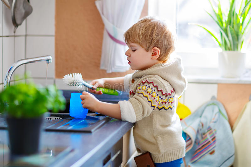 Mały berbeć pomaga w kuchni z domycie naczyniami obraz royalty free
