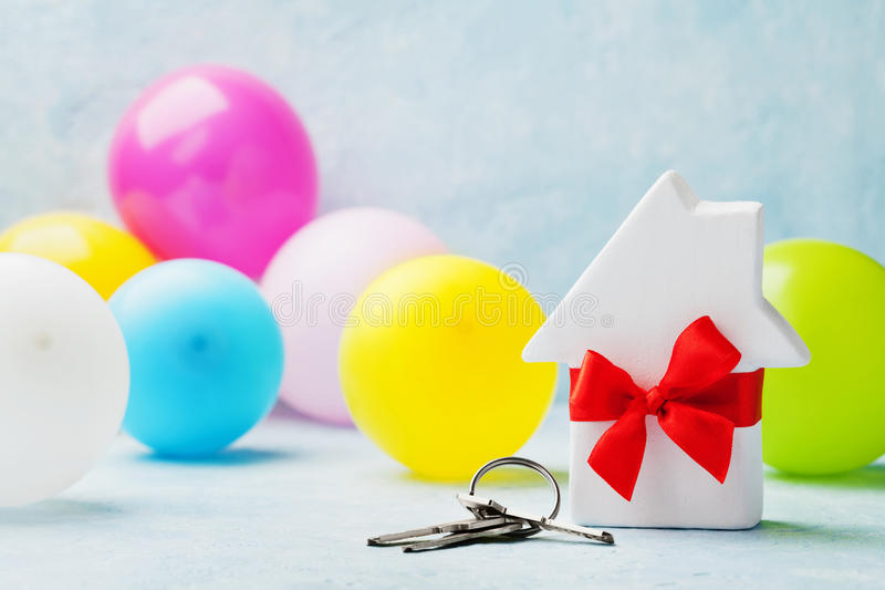 Mały biały drewniany dom dekorujący czerwony łęku faborek z wiązką klucze i balony Parapetówa, prezent, chodzenie, kupienie nowy  obrazy stock