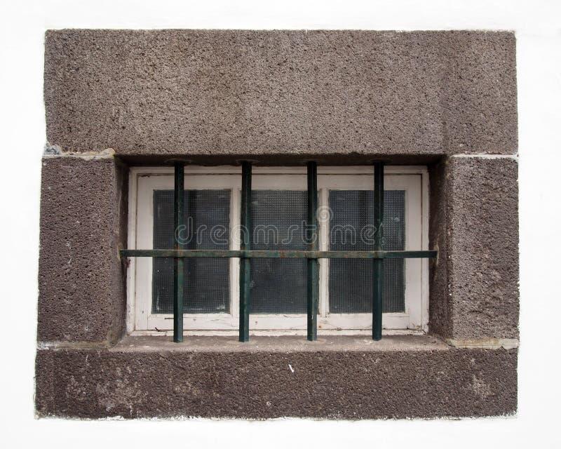 Mały biały drewniany okno z szklanymi taflami zakrywać stalowymi barami w ampuła kamienia popielatej ramie na białej ścianie obrazy royalty free