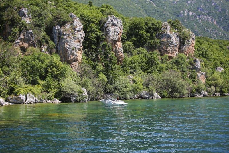 Mały biały jacht blisko skalistego brzeg na pięknym Jeziornym Ohrid, republika Północny Macedonia zdjęcia royalty free