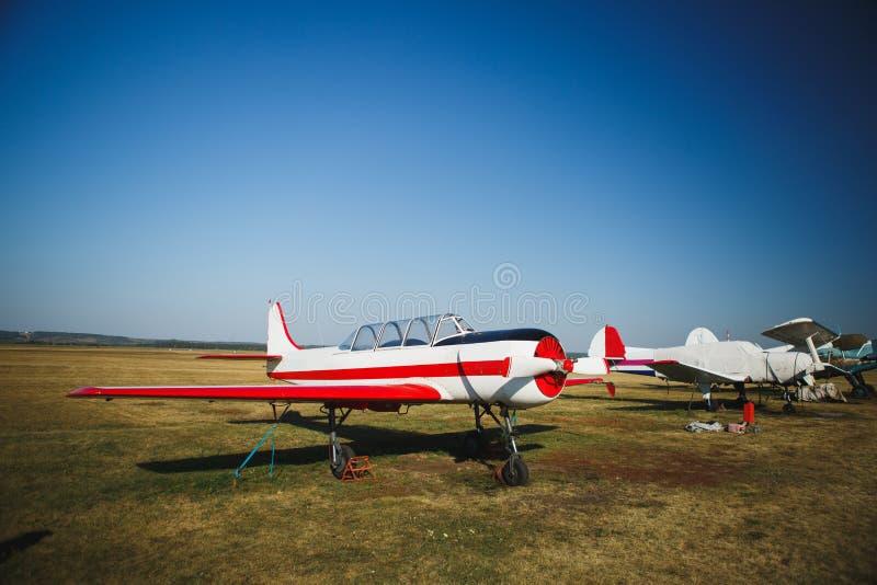 Mały biel z czerwień samolotu stojakami na trawie zdjęcie stock